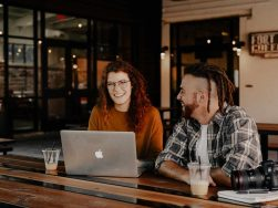 man and woman sitting in front of silver macbook
